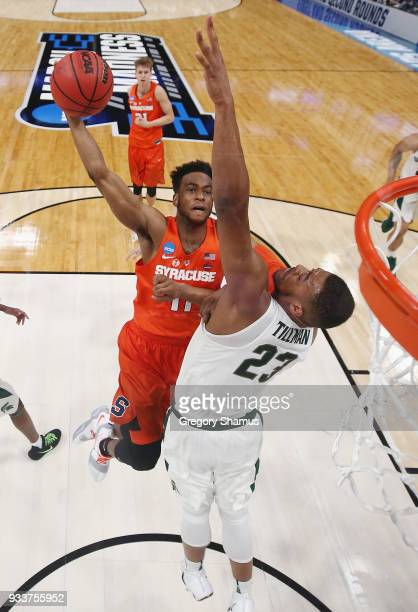 Oshae Brissett of the Syracuse Orange drives to the basket against Xavier Tillman of the Michigan State Spartans in the second round of the 2018 NCAA...