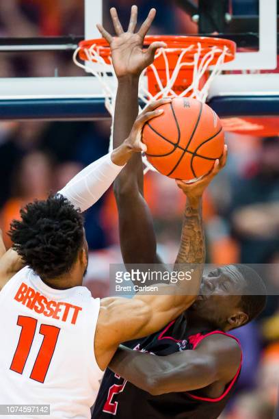 Oshae Brissett of the Syracuse Orange shoots the ball as he collides with Salif Boudie of the Arkansas State Red Wolves during the first half at the...