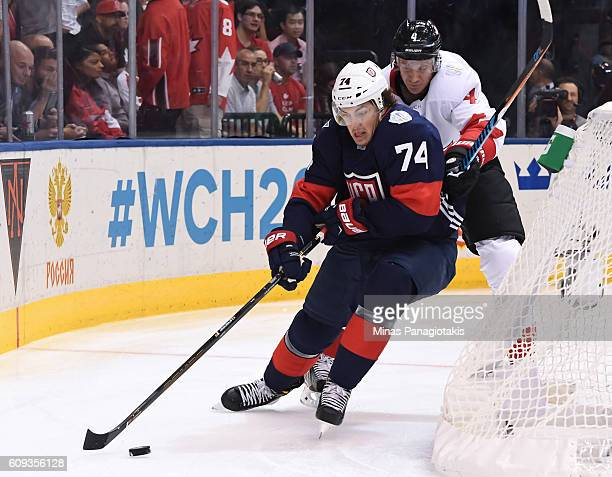 J Oshie of Team USA stickhandles the puck with pressure from Jay Bouwmeester of Team Canada during the World Cup of Hockey 2016 at Air Canada Centre...