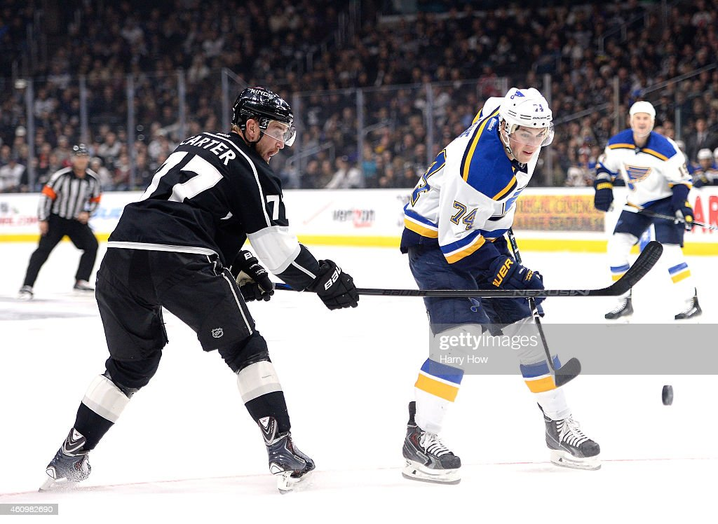 T.J. Oshie #74 of the St. Louis Blues has the puck knocked away by Jeff Carter #77 of the Los Angeles Kings at Staples Center on December 18, 2014 in Los Angeles, California.