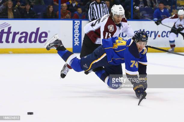 J Oshie of the St Louis Blues is tripped up by PA Parenteau of the Colorado Avalanche while pursuing a loose puck at the Scottrade Center on November...