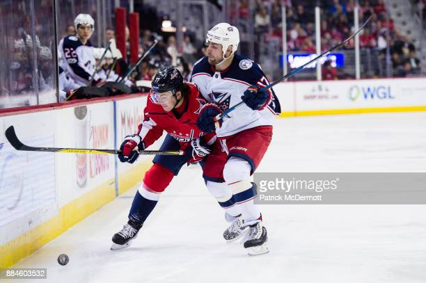 J Oshie of the Washington Capitals and Brandon Dubinsky of the Columbus Blue Jackets battle for the puck in the third period at Capital One Arena on...