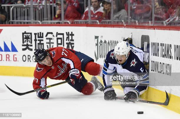 J Oshie of the Washington Capitals and Dmitry Kulikov of the Winnipeg Jets battle for the puck in the first period at Capital One Arena on March 10...