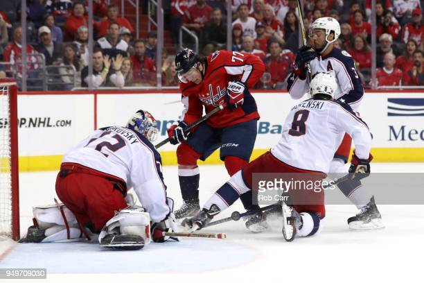 J Oshie of the Washington Capitals and Zach Werenski and goalie Sergei Bobrovsky of the Columbus Blue Jackets go after the puck in overtime during...