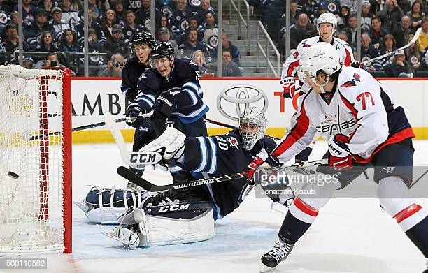 J Oshie of the Washington Capitals backhands the puck wide of the net as goaltender Connor Hellebuyck of the Winnipeg Jets looks on during third...