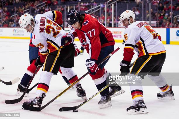 J Oshie of the Washington Capitals battles for the puck against Sean Monahan and Mark Giordano of the Calgary Flames in the third period at Capital...