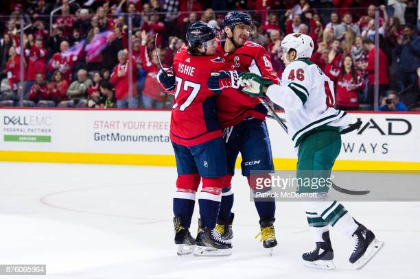 J Oshie of the Washington Capitals celebrates with Alex Ovechkin after scoring a first period goal against the Minnesota Wild at Capital One Arena on...