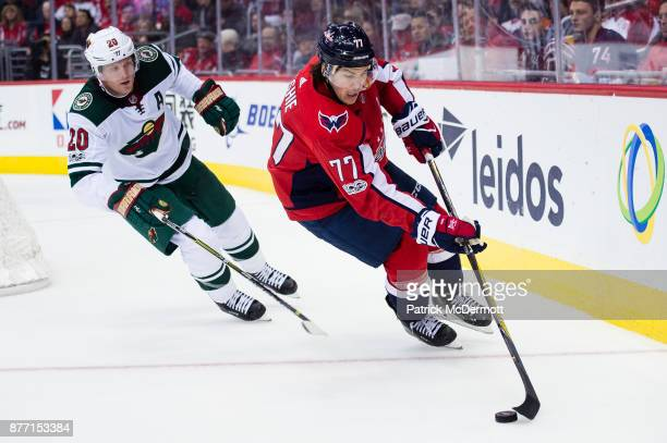 J Oshie of the Washington Capitals controls the puck against Ryan Suter of the Minnesota Wild in the third period at Capital One Arena on November 18...