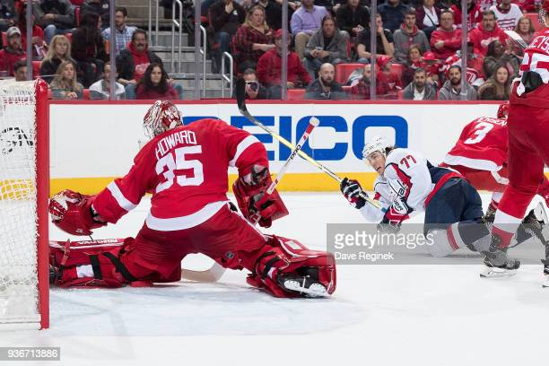 J Oshie of the Washington Capitals falls as he takes a shoot on goaltender Jimmy Howard of the Detroit Red Wings during an NHL game at Little Caesars...