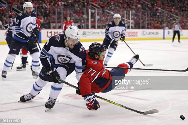 J Oshie of the Washington Capitals is checked by Jacob Trouba of the Winnipeg Jets during the second period at Capital One Arena on March 12 2018 in...
