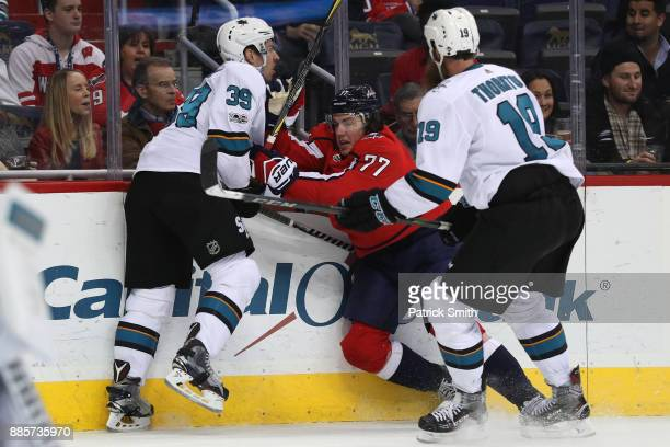 J Oshie of the Washington Capitals is checked by Logan Couture and Joe Thornton of the San Jose Sharks during the second period at Capital One Arena...