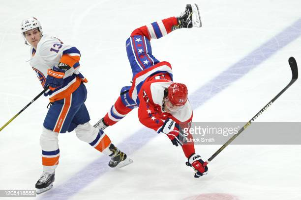 Oshie of the Washington Capitals is checked by Mathew Barzal of the New York Islanders during the third period at Capital One Arena on February 10,...