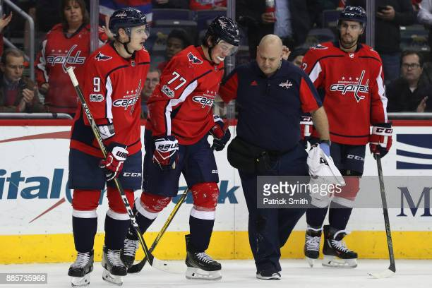 J Oshie of the Washington Capitals is helped offo f the ice after being injured against the San Jose Sharks during the second period at Capital One...