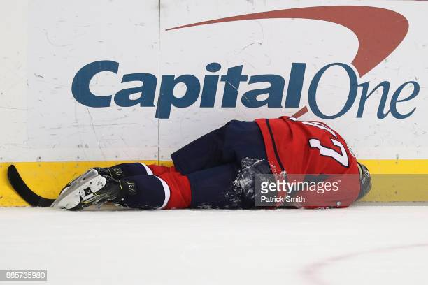 J Oshie of the Washington Capitals lays on the ice injured against the San Jose Sharks during the second period at Capital One Arena on December 4...