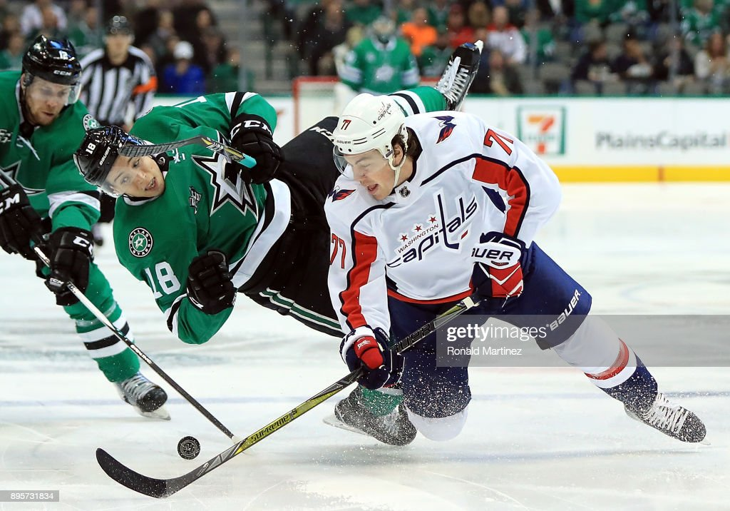 T.J. Oshie #77 of the Washington Capitals skates the puck against Tyler Pitlick #18 of the Dallas Stars in the first period at American Airlines Center on December 19, 2017 in Dallas, Texas.