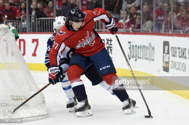 J Oshie of the Washington Capitals skates with the puck against Mark Scheifele of the Winnipeg Jets in the first period at Capital One Arena on March...