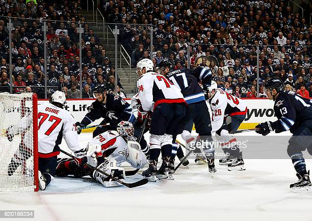 J Oshie of the Washington Capitals slides behind goaltender Braden Holtby to stop the puck as Joel Armia of the Winnipeg Jets tries to score during...