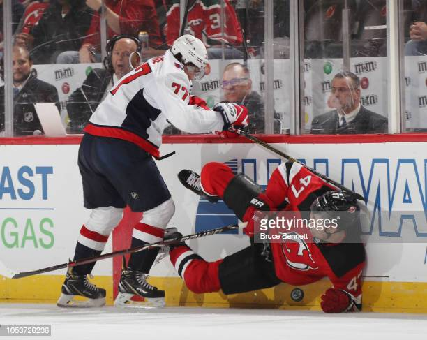 Oshie of the Washington Capitals steps into John Quenneville of the New Jersey Devils during the third period at the Prudential Center on October 11,...