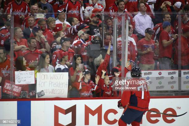 J Oshie of the Washington Capitals throws a puck to a fan during warmups prior to Game Four of the 2018 NHL Stanley Cup Final against the Vegas...
