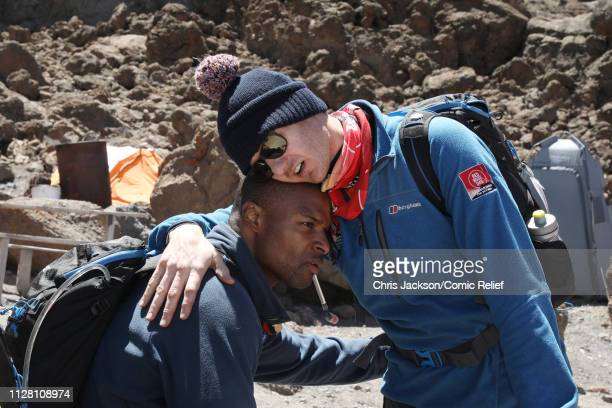 Osi Umenyiora and Dan Walker hug during day six of of 'Kilimanjaro The Return' for Red Nose Day on February 28 2019 in Arusha Tanzania all to raise...
