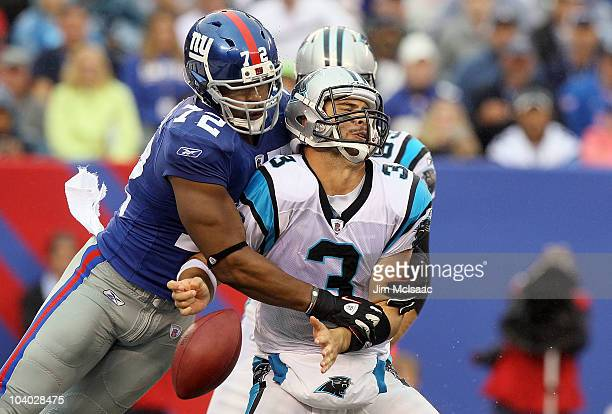 Osi Umenyiora of the New York Giants forces a fumble against Matt Moore of the Carolina Panthers during the fourth quarter on September 12 2010 at...