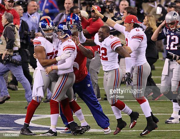 Osi Umenyiora Steve Weatherford David Carr and Derrick Martin and the New York Giants celebrate in front of Tom Brady of the New England Patriots...