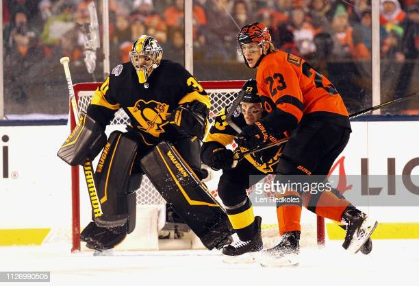 Oskar Lindblom of the Philadelphia Flyers battles for position with Jack Johnson of the Pittsburgh Penguins in front of Matt Murray at the 2019 Coors...