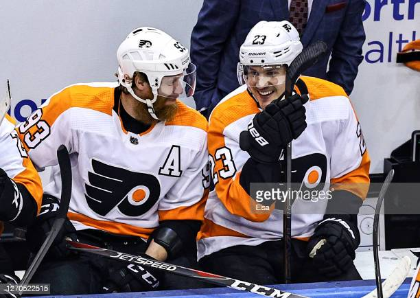 Oskar Lindblom of the Philadelphia Flyers shares a laugh with Jakub Voracek during a timeout against the New York Islanders during the first period...