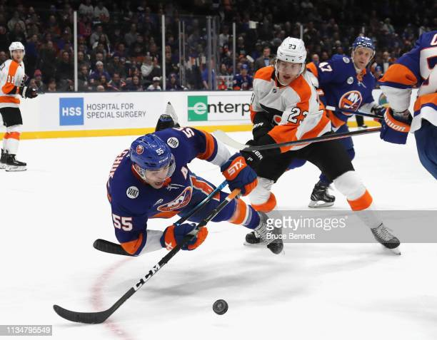 Oskar Lindblom of the Philadelphia Flyers trips up Johnny Boychuk of the New York Islanders during the first period at NYCB Live's Nassau Coliseum on...