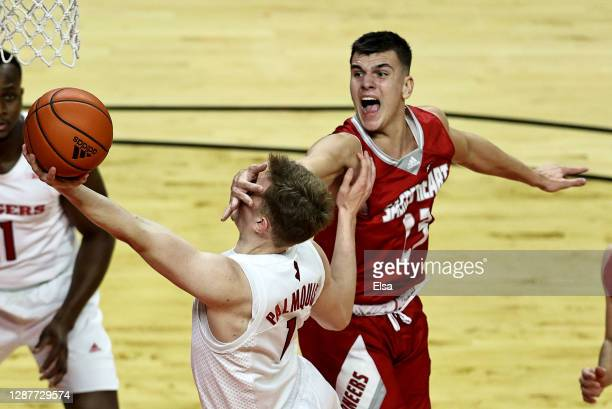 Oskar Palmquist of the Rutgers Scarlet Knights is fouled by Matas Spokas of the Sacred Heart Pioneers during the season opening game at Rutgers...