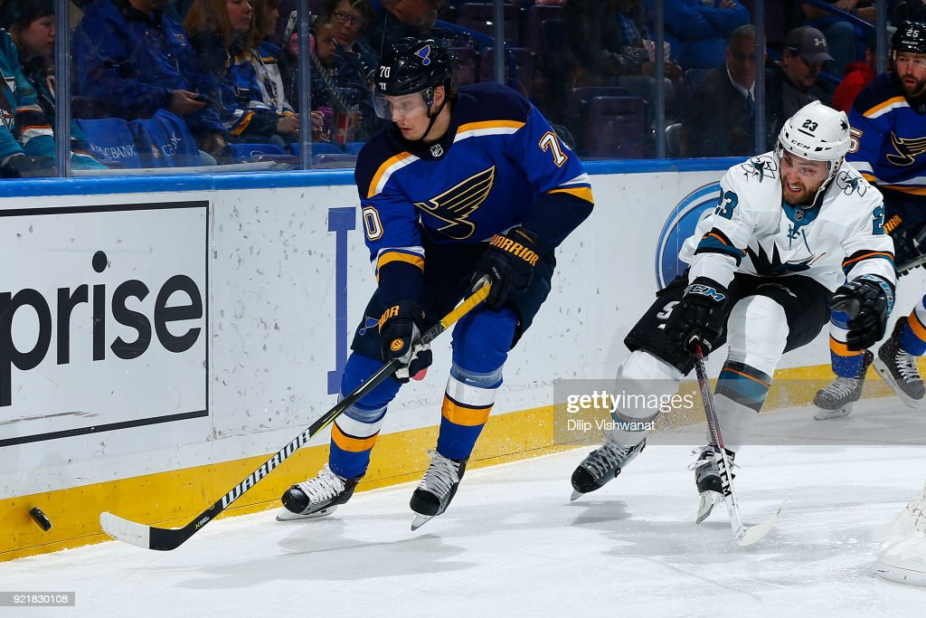 Oskar Sundqvist #70 of the St. Louis Blues beats Barclay Goodrow #23 of the San Jose Sharks to the puck at Scottrade Center on February 20, 2018 in St. Louis, Missouri.