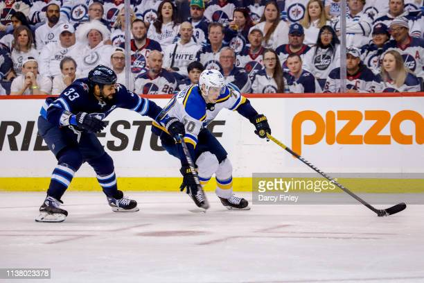 Oskar Sundqvist of the St Louis Blues plays the puck down the ice as Dustin Byfuglien of the Winnipeg Jets gives chase during third period action in...