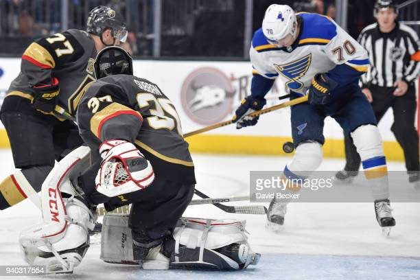 Oskar Sundqvist of the St Louis Blues tries to control a rebound with Brad Hunt and Malcolm Subban of the Vegas Golden Knights defending during the...