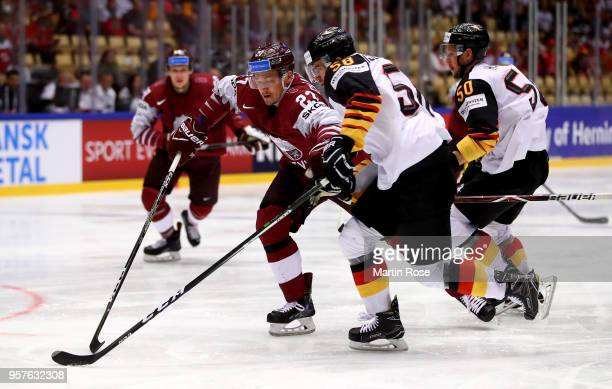 Oskars Cibulskis of Latvia and Markus Eisenschmid of Germany battle for the puck during the 2018 IIHF Ice Hockey World Championship Group B game...