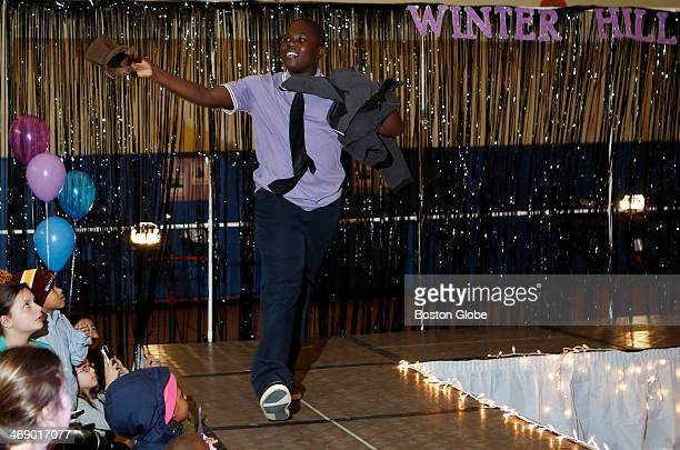 Oskervens Lenues a seventh grader tosses his hat into the crowd as he walks down the runway during a school fashion show of new dress policy options...
