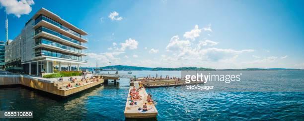 Oslo people enjoying summer sunbathing on Aker Brygge waterfront Norway