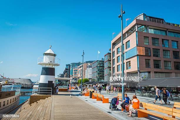 Oslo people enjoying summer sunshine on Aker Brygge waterfront Norway