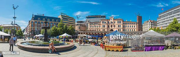 Oslo Youngstorget panorama people enjoying sunshine and market stalls Norway