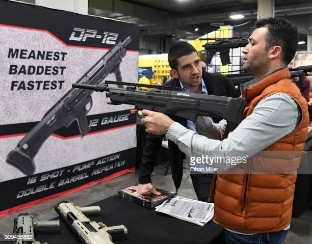 Osman Gulle and Ibrahim Ozerbas both of Turkey look at a SKOBULL semiautomatic shotgun at the Standard Manufacturing Co booth at the 2018 National...