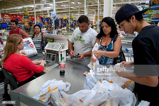 Osmar Fernandes center his wife Silvia Helena center right and son Lucas right pay for their purchases at a WalMart supercenter store in Sao Paulo...