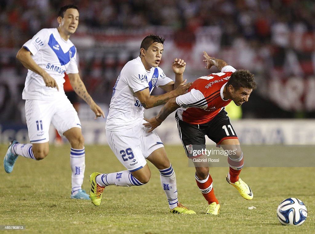 Osmar Ferreyra of River Plate fights for the ball with Alan Aguirre of Velez Sarsfield during a match between River Plate and Velez Sarsfield as part of 15th round of Torneo Final 2014 at Monumental Antonio Vespucio Liberti Stadium on April 12, 2014 in Buenos Aires, Argentina.