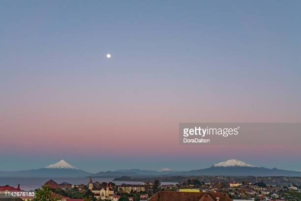 Osorno Volcano, Volcán Calbuco and Moon at dusk panoramic in Chilean Lake District - Puerto Varas, Chile