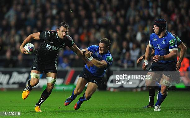 Ospreys player Joe Bearman breaks the tackle of Leinster fly half Jimmy Gopperth during the Heineken Cup Pool1 game between Ospreys and Leinster at...