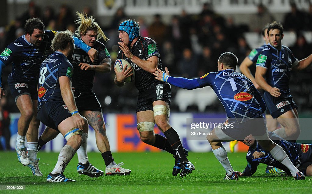 Ospreys player Justin Tipuric (c) runs at the Castres defence during the Heineken Cup pool 1 round 4 match between Ospreys and Castres Olympique at Liberty Stadium on December 13, 2013 in Swansea, Wales.