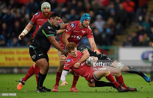 Ospreys player Justin Tipuric tackles Rhys Patchell of the Scarlets during the Guinness Pro 12 match between Ospreys and Scarlets at Liberty Stadium...
