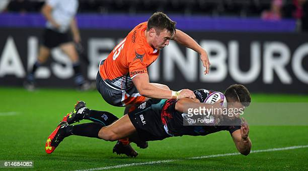 Ospreys scrum half Rhys Webb dives over to score the second try despite the attentions of Brett Connon of the Falcons during the European Rugby...