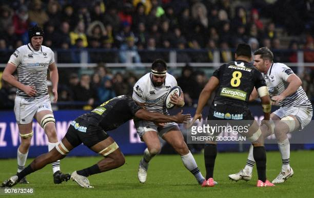 Ospreys' Welsh hooker Scott Baldwin is tackled by Clermont's Fidjian flanker Peceli Yato during the European Rugby Champions Cup rugby union match...