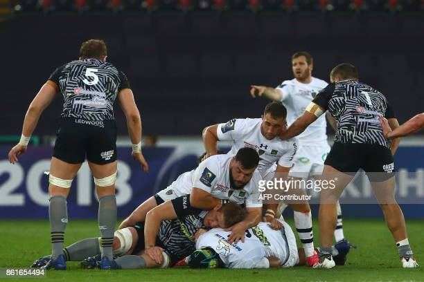 Ospreys' Welsh lock Bradley Davies is tackled by Clermont's prop Rabah Slimani Clermont's French scrumhalf Morgan Parra and Clermont's French lock...