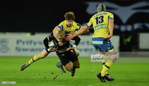 Ospreys wing Eli Walker is tackled by David Strettle and Jonathan Davies of Clermont during the European Rugby Champions Cup Pool 2 match between...