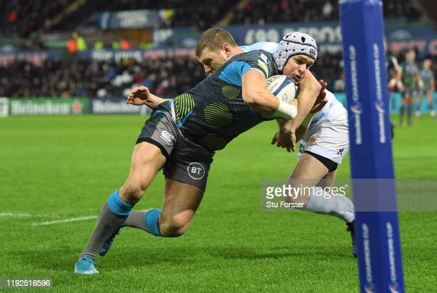 Ospreys wing Hanno Dirksen brushes past Finn Russell to score the first try during the Heineken Champions Cup Round 3 match between Ospreys and...